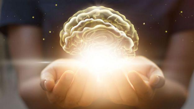 Ilustración de un cerebro iluminado sobre las manos de una mujer