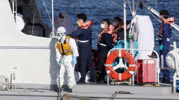 Asistentes médicos transfieren a una persona contagiada (en la foto, envuelta en una sábana blanca) desde el crucero al bote de rescate.