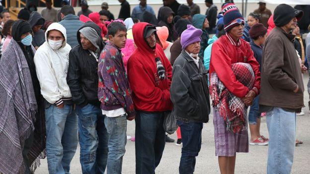 Fila de migrantes en un puesto fronterizo entre Estados Unidos y México.