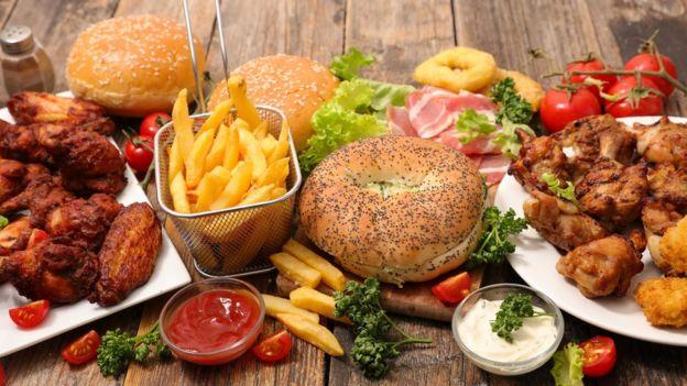 Variedad de comida que incluye hamburguesa, pollo, papas fritas, etc.