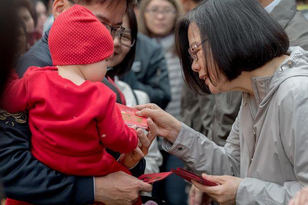 台灣總統蔡英文在宮廟前發紅包。