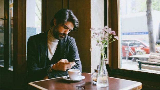 Homem olha celular enquanto toma café