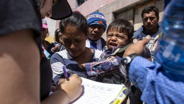 Una mujer migrante da sus datos a una mujer que anota en una planilla