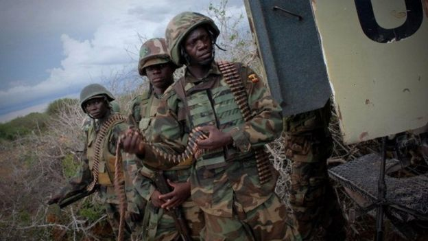 Soldiers serving with the African Union Mission in Somalia walk in front of an armoured personnel carrier on May 22, 2012
