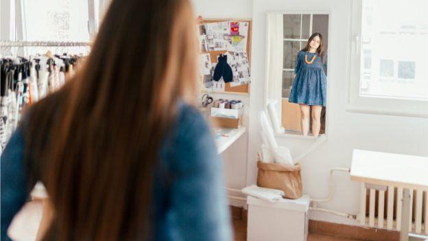 Mulher se olha no espelho com olhar desanimado