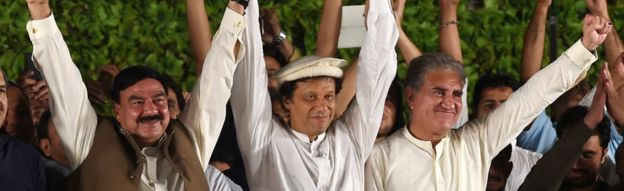Chairman of Pakistan's Tehreek-e-Insaf (PTI) party, Imran Khan (centre), greets the audience during a rally on 14 August 2017