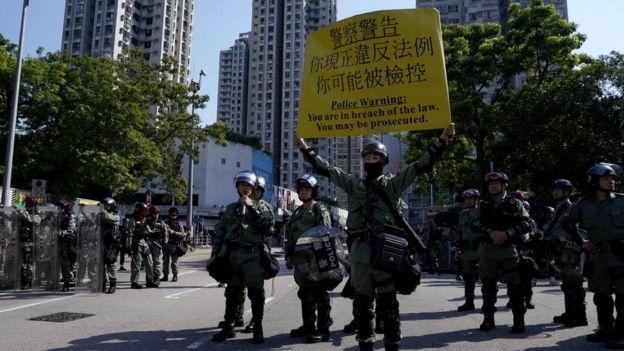 香港新界屯门防暴警察向示威群众展示警告旗号(21/9/2019)