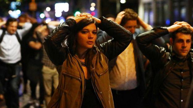 在場民眾雙手置於頭上配合警方疏散。