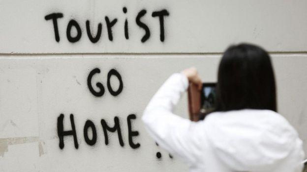 سائحة تلتقط صورة لكتابات جدارية تحض السياح على مغادرة برشلونة، في إسبانيا العام الماضي