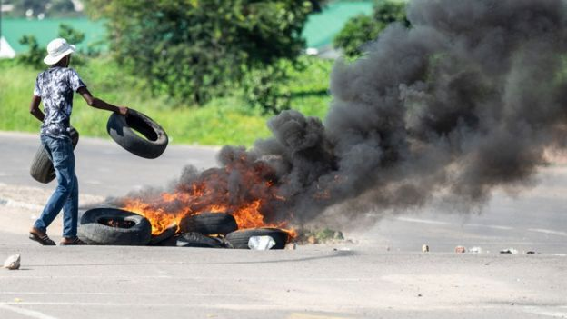 """A protesters burns tyres on a road during a """"stay-away"""" demonstration against the doubling of fuel prices"""