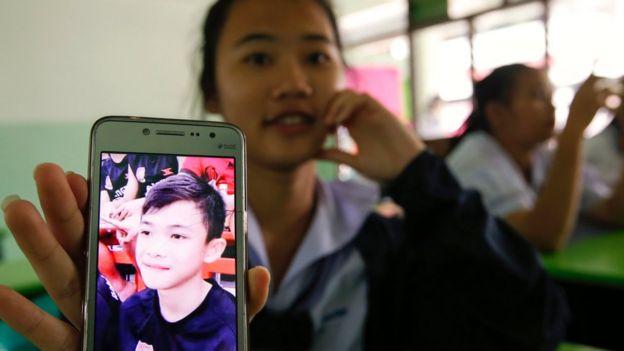 Una estudiante muestra en su celular una foto de Duangpetch Promthep, uno de los niños atrapados