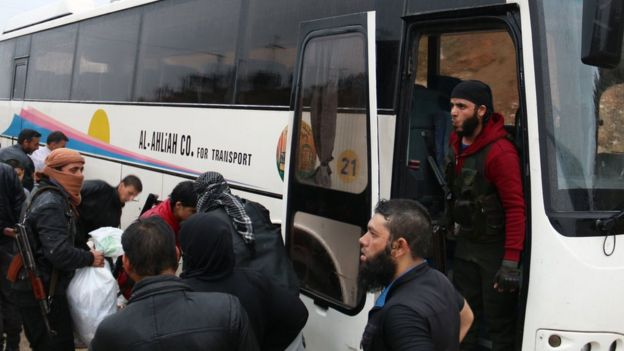 Rebels board a bus in Rastan, Syria, 7 May