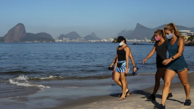 People walk wearing a protective mask on Icarai beach, as the Sugarloaf Mountain is seen in the distance, during the coronavirus (COVID-19) pandemic on May 21, 2020 in Niteroi, Brazil