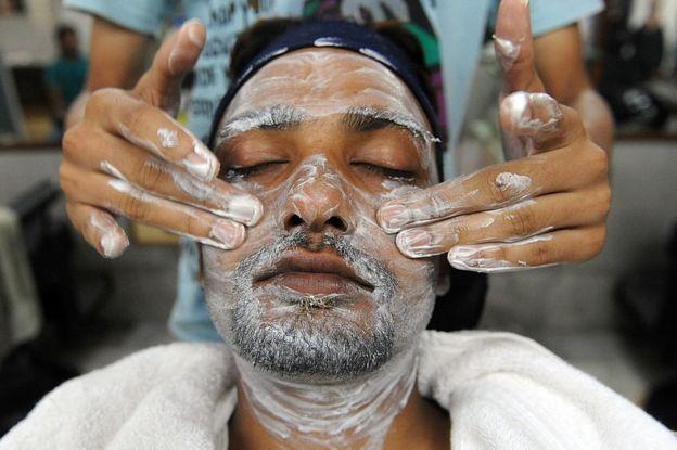 Un hombre al que le está siendo aplicado un cosmético.