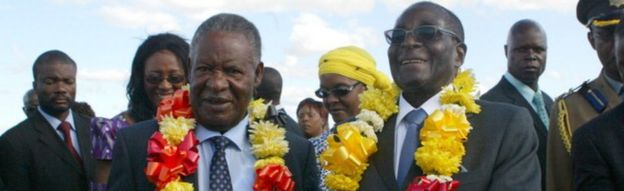 Robert Mugabe (R) welcomes Zambian President Michael Sata (L) upon his arrival in Harare on April 25, 2012 for a two-day state visit