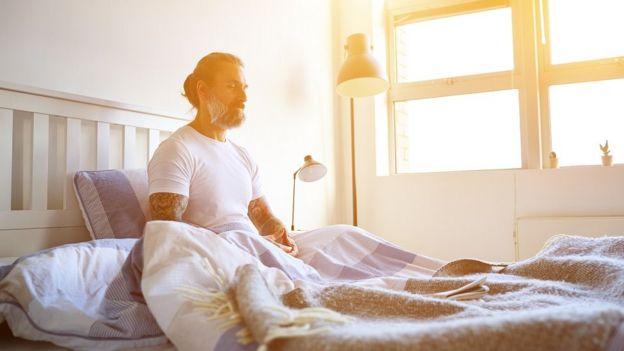 Homem acorda com a luz natural que entra no quarto pela janela
