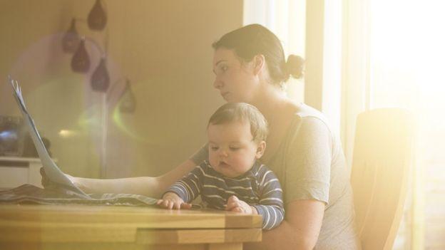 Mulher com bebê no computador