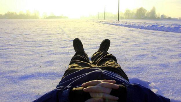 Homem deitado na neve, descansando