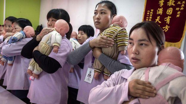 Diversas mulheres em aula segurando bonecos de bebês