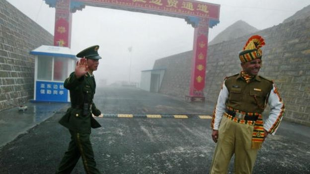 A Chinese soldier and an Indian soldier stand guard at the Chinese side of the ancient Nathu La border crossing between India and China in 2008