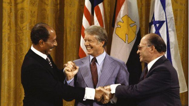 الرئيس الأمريكي السابق جيمي كارتر يتوسط نظيره المصري أنور السادات (يسار) ورئيس الحكومة الإسرائيلية مناحيم بيغن لدى توقيع معاهدة كامب ديفيد