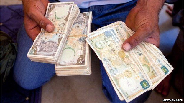A man holding wads of Syrian pound notes