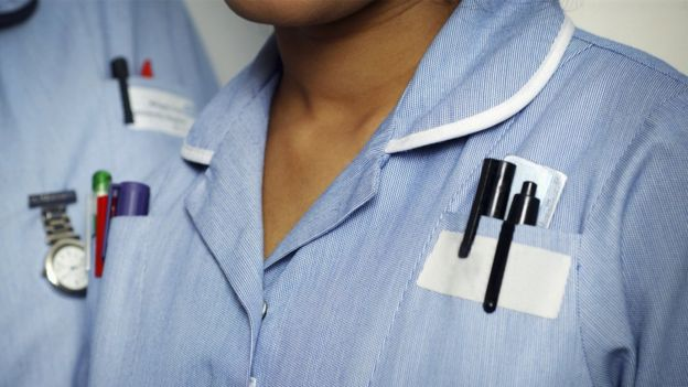 Close-up of two typically dressed NHS nurses
