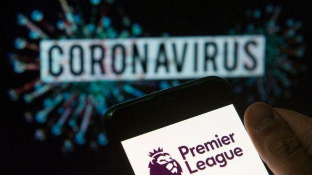"""شعار الدوري الإنجليزي الممتاز يظهر في هاتف ذكي ويقابله عبارة """"فيروس كورونا"""""""