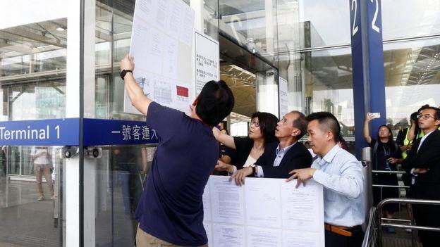 机场职员在客运大楼外张贴香港法庭的命令,限制示威者的集会范围。