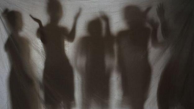 Sombras de mulheres atrás de um tecido