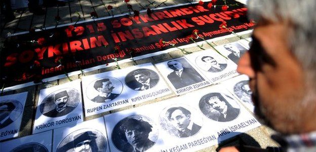 """A person looks at portraits and a sign reading """"1915 is a Genocide. Genocide is a crimes against humanity"""" during a demonstration on 24 April 2013 in Istanbul"""