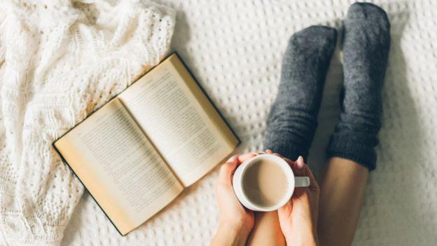 Persona con un libro abierto en la cama y una taza de café.