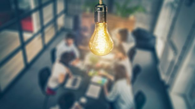 Una reunión con una lámpara en primer plano.