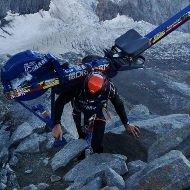 Matthew Disney escala una montaña con una máquina de remo.