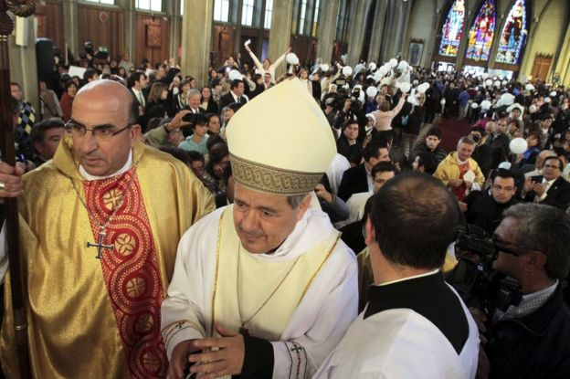 Bishop Juan Barros (C) attends his first religious service as people protest against him at the Osorno cathedral, south of Santiago, Chile, 21 March 2015