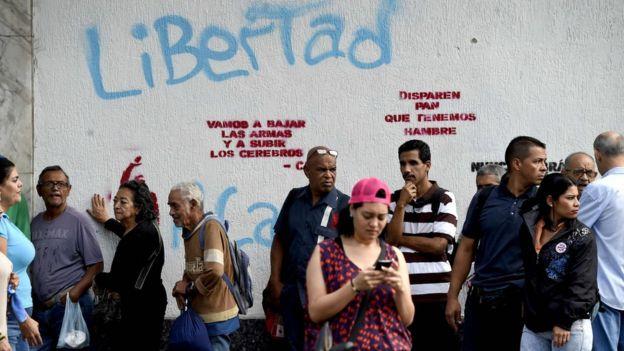 Una fila de personas espera que llegue el autobús en Caracas.