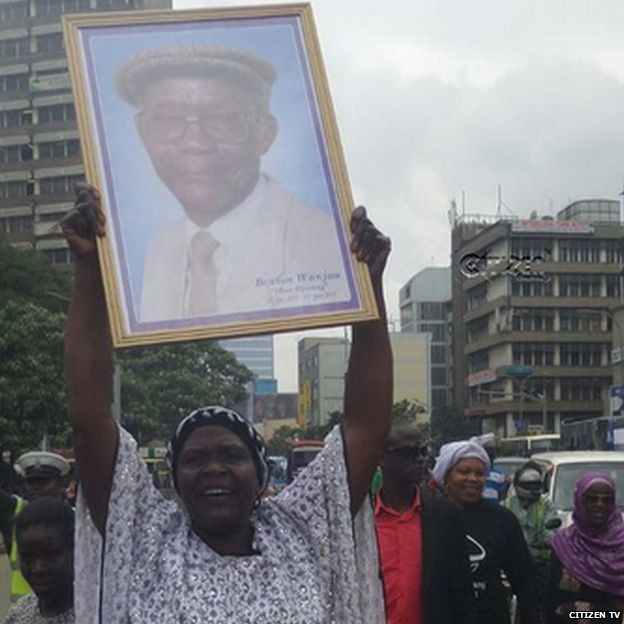 Woman holding up picture of Mzee Ojwang