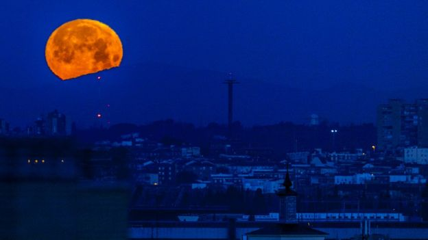 The bright orange moon set against a deep blue cityscape of Madrid, Spain
