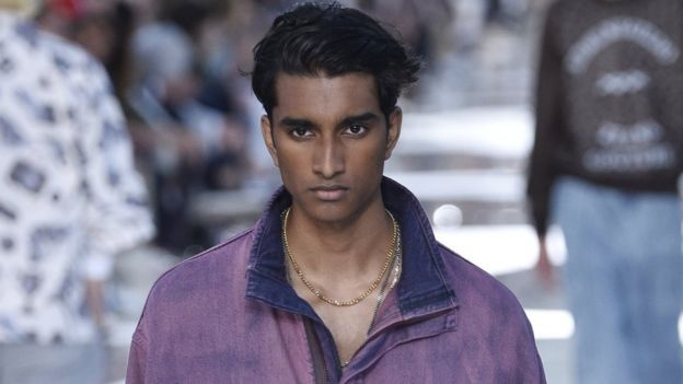 Jeenu Mahadevan in a purple jacket and gold chain, modelling at the Ermenegildo Zegna show at Milan Men's Fashion Week in June 2018