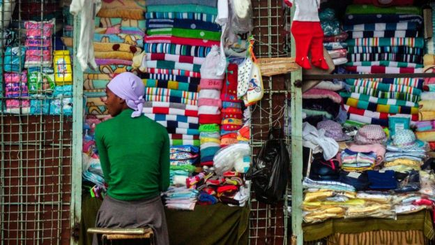 A vendor sits at a stall selling cloth towels, hats and other textiles in the Zimbabwean capital Harare on November 16, 2017