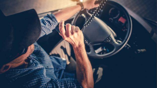 Camionero habla por un intercomunicador.