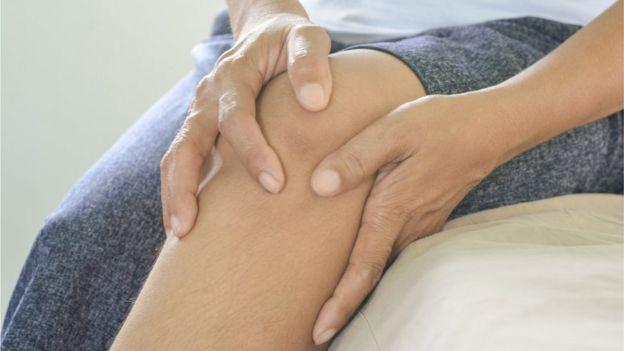 Mujer agarrándose la rodilla.