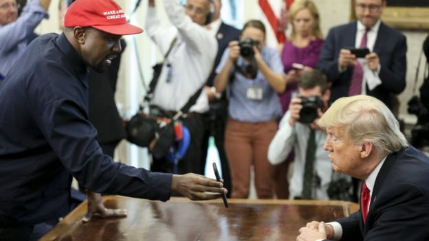 Rapper Kanye West shows a picture of a plane on a phone to US President Donald Trump during a meeting in the White House Oval Office, 11 October 2018