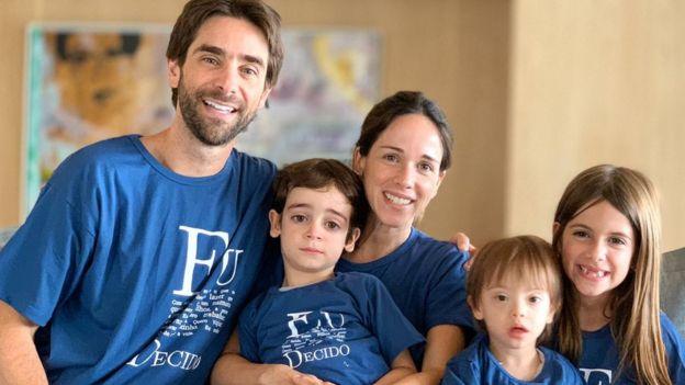 Pais de Pedro Zylberstajn e seus dois irmãos posam sorrindo para foto dentro de sala