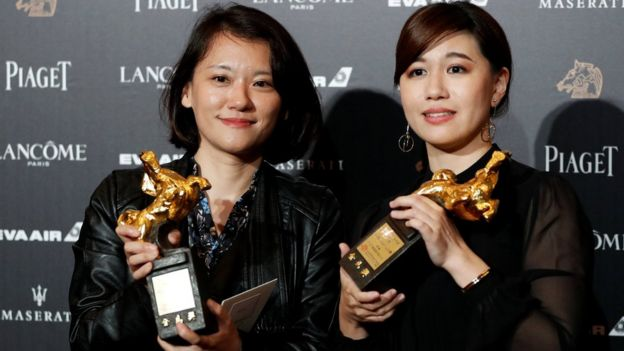 Taiwanese director Yue Fu (R) poses backstage after winning Best Documentary for her movie Our Youth in Taiwan