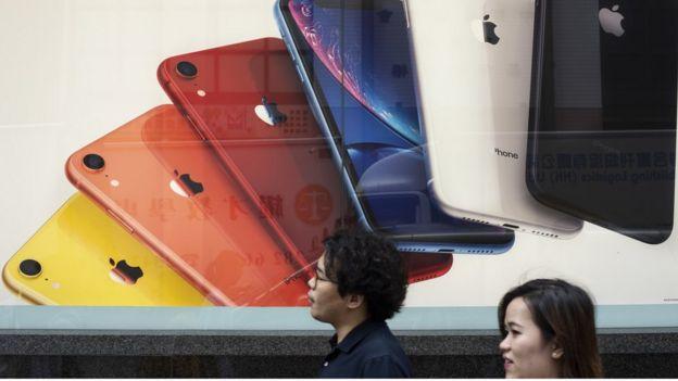 Pedestrians walk past an Apple Iphone advertisement in Hong Kong.