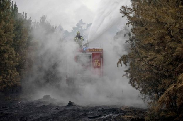 Firefighters on a truck blast water at a smoke-clouded forest, surrounded by blackened earth