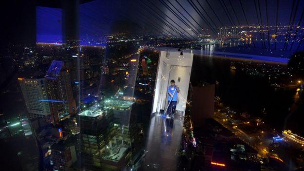 Một nhân viên lao công lau dọn ở tầng skyview của tòa nhà Bitexco, tòa nhà cao nhất Việt Nam