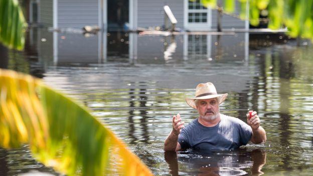 Hombre con el agua a la altura del pecho en Carolina del Sur tras el huracán Florence en setiembre de 2018