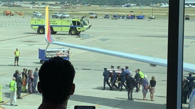 Các nhân viên sân bay đứng nghiêm khi linh cữu cựu binh Col Knight được đưa ra khỏi máy bay